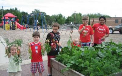several children next to a raised garden