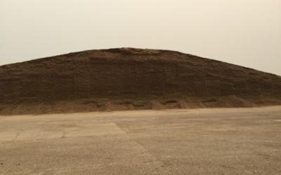 A large pile of silage on a farm lot.