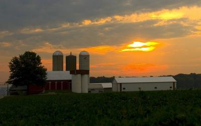 A family farm with the sun setting in the background.