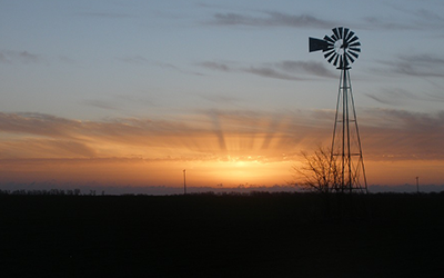 a windmill in front of a sunset