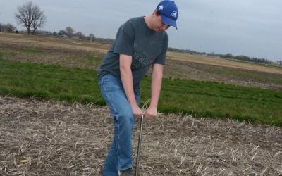 A young man driving a soil sampling tool into a soybean field