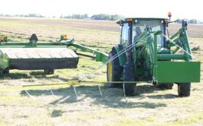 A green front-end-loader pulling a hay mower with a flushing bar.