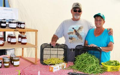 A husband and wife displaying fresh produce at a farmer's market stand.