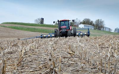 A red tractor and seed drill planting in a no-till field.