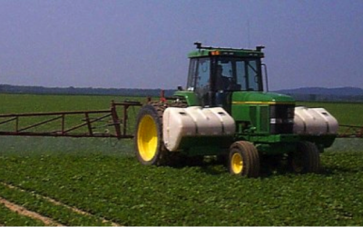 a tractor in a field spraying soybeans