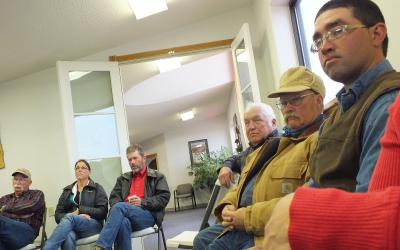 A group of farmers and ranchers sitting at a meeting