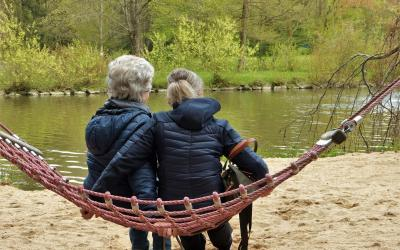 two people sitting on a rope swing