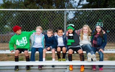 Diverse group of school-age children sitting on bleachers outside in 4-H clothing.; Photos; 4-H Grows Here; Brand; 4-H youth