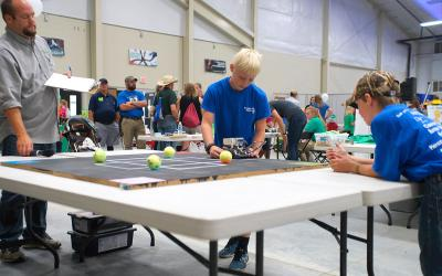 Two young males participating in the robotics challenge at the South Dakota State Fair