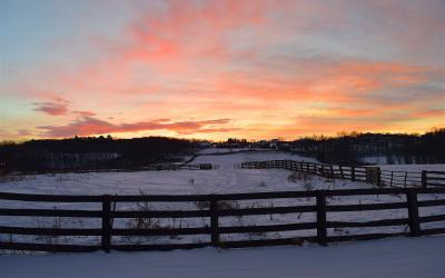 Sun rising over a ranch during winter.