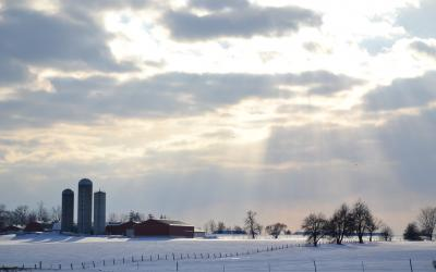 A snowy farmyard with sunlight breaking through the clouds.