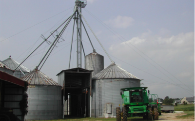 A group of grain bins with a green harvester in front.