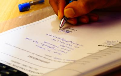 A hand writing on a financial document with a pen.