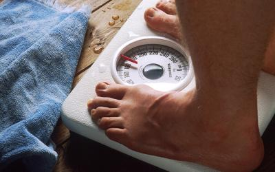 Close-up of the feet of a man standing on a bathroom scale with a blue towel lying nearby.