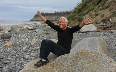 A happy, older adult sitting on a rock by the seashore.