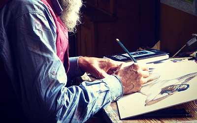 older man sketching a person