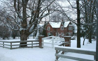 A snowy yard outside a red, brick house.