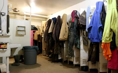 row of lockers with several employee jackets, hats, and clothing hanging outside.