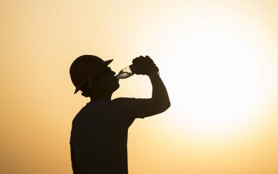 Silhouette of worker drinking water in extreme heat.