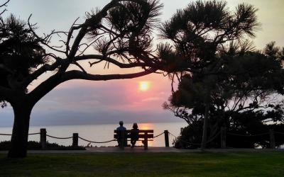 Two older adults watching a sunset on a park bench.