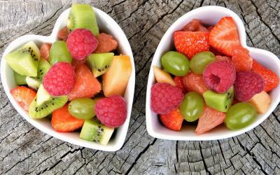 two heart-shaped bowls filled with mixed fruit