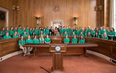 large group of 4-H youth posing for a photo with U.S. government officials inside a governmental chamber