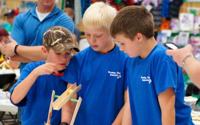 three male 4-H youth inspecting a catapult that they built