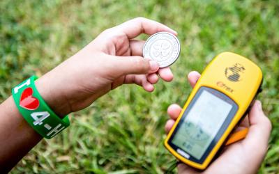 hands holding a 4-H coin and a gps navigational device