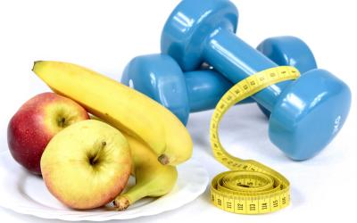 apples and bananas sitting on a plate next to a set of blue hand weights and a body measuring tape