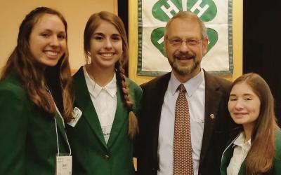 three female 4-H youth standing with and older adult male official