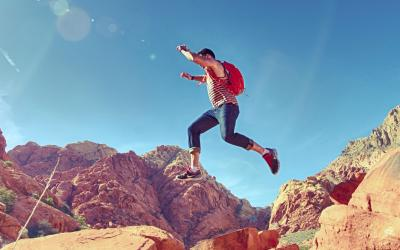 male youth bounding over desert rock formations