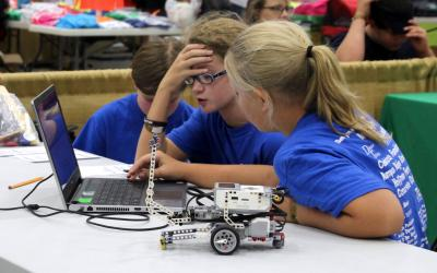 two male and one female 4-H youth inspecting a robotics control program on a laptop