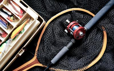 fishing net and rod next to tackle box