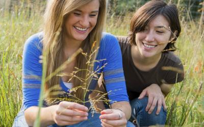 two female youth inspecting a plant in a pasture