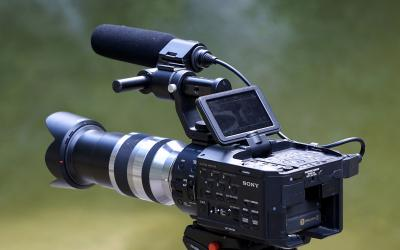 a digital camera with an onboard boom microphone on a tripod.