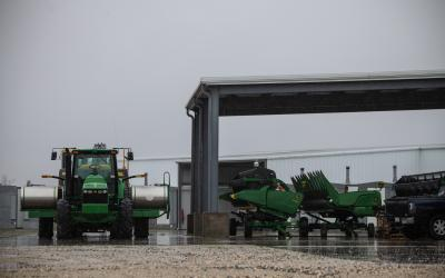 green tractor next to a machine shed with farm equipment inside it