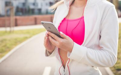 young woman in jogging outfit reading information on her phone