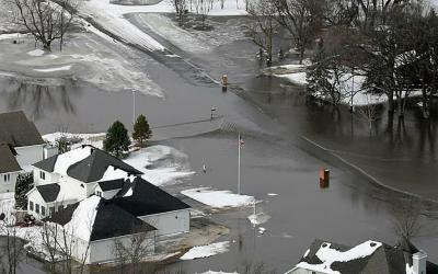neighborhood street flooded with melted snow and water runoff. FEMA News Photo