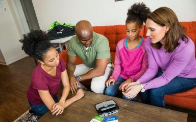 family gathered around an emergency weather radio