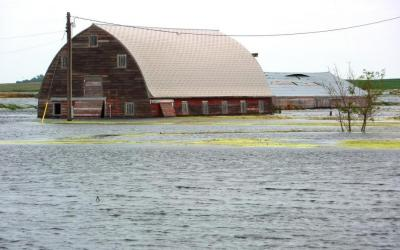 abandoned barn surrounded by flood waters. Photo by Jeannie Mooney, FEMA