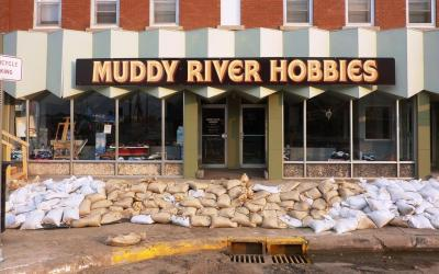 "Small business ""Muddy River Hobbies"" with sandbags in front of entrance. Photo by Jeannie Mooney, FEMA."