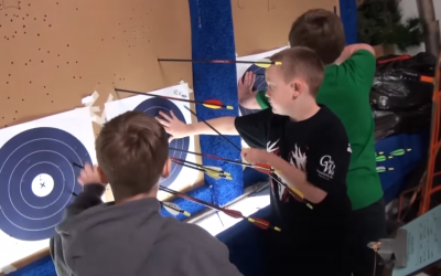 three male 4-H youth retrieving arrows from archery targets