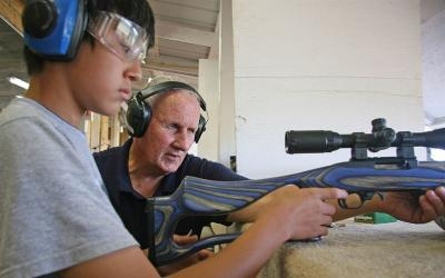 4-H youth with shooting instructor preparing to fire a rifle