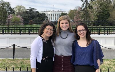an image of three young women standing outside the White House.