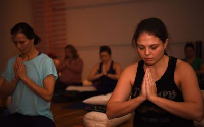 group of young women meditating during a yoga session