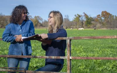 femal rancher with young female training reviewing paperwork beside a cow pasture