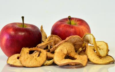two whole apples behind a small pile of dehydrated apple slices