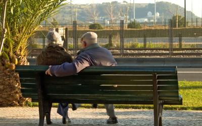 retired couple sitting on a park bench overlooking a bluff.