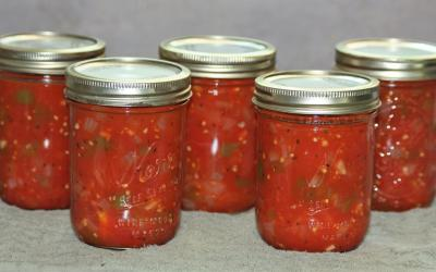 Five jars of canned stewed tomatoes sitting on a gray kitchen towel with a gray background.