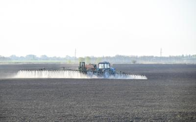 A sprayer applying pre-emergent pesticide to a bare field.